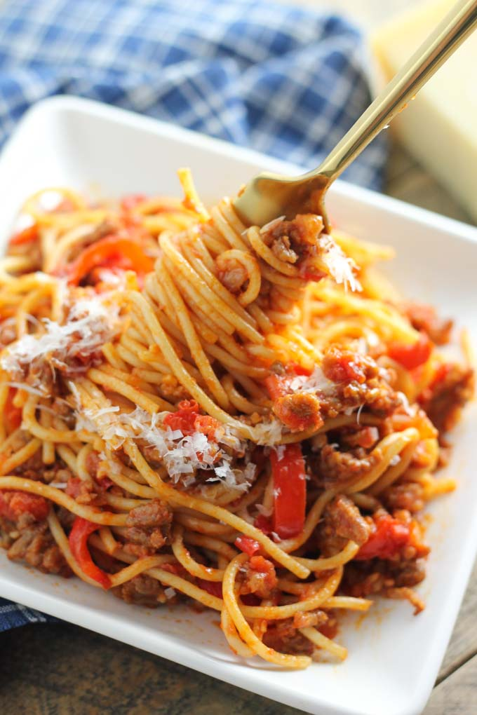 A hearty ground beef and tomato pasta sauce is mixed with spaghetti and topped with an Italian sausage and melted Parmesan cheese Great for Presidents Day